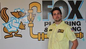 Plumber in yellow shirt standing in front of sign