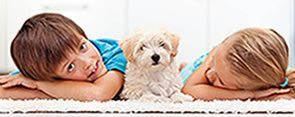 Children laying down next to white puppy